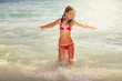 Happy girl jump on the sea waves in summer vacation