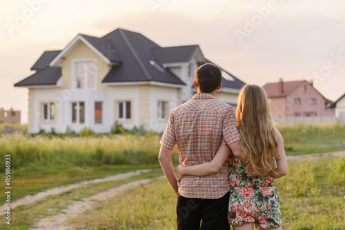Fototapeta rear view of young couple looking at their new house obraz