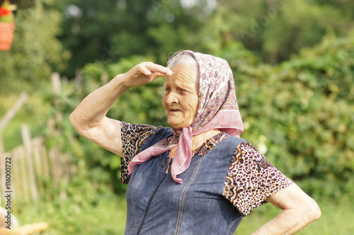 Valokuva  grandmother in a headscarf holding her hand in the face and looks into the dista