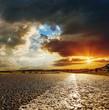 low orange sunset in dramatic clouds over asphalt road