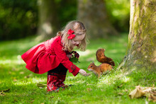 Little Girl Feeding Squirrel