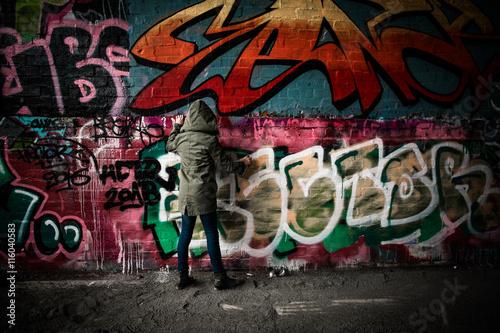 Photo Stands Graffiti Hooded girl finishing graffiti
