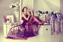 Young Girl In Dress With A Train Marsala Color Sitting On A Luxury High Chair With Flowers On The Background Of The Fashion Interior And Triangular Pattern.