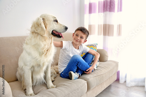 Small boy and cute dog on couch Canvas Print