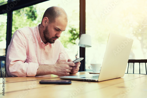 Fototapety, obrazy: Young freelancer use smart phone sitting in modern loft interior with laptop computer