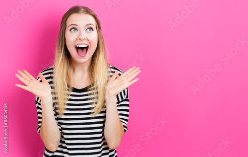 Fotografija  Happy young woman posing on pink background