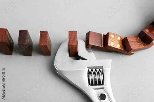 Valokuva  Dominoes and wrench on grey background
