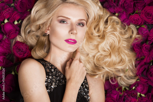 Foto  Beautiful blond girl lying on background of roses