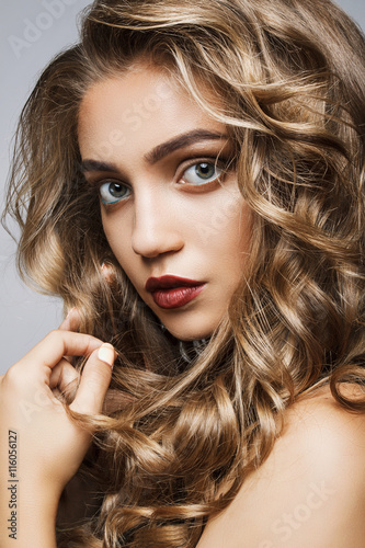 Fototapeta Beautiful girl with long wavy hair . fair-haired model with curl