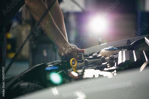 Fototapeta Auto mechanic repair engine in a car repair shop obraz