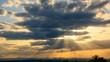 Goldene Sonnenstrahlen fallen effektvoll durch ziehende dunkle Wolken