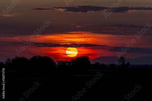 Tuinposter Bordeaux Red sunset bhind the clouds