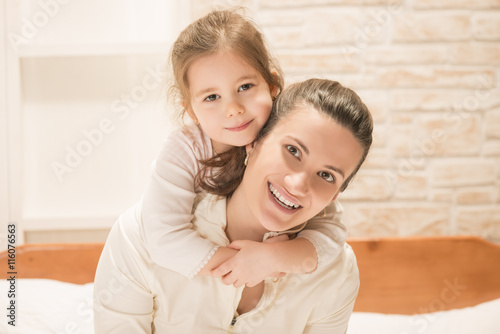 Fotografia  Beautiful little girl embracing her mother while sitting on the bed at home