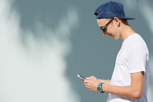 Profile Of Smiling High School Student Boy Wearing Shades And Snapback Holding Mobile Phone, Messaging Via Social Networks, Posing Against White Copy Space Wall For Your Text Or Advertising Content