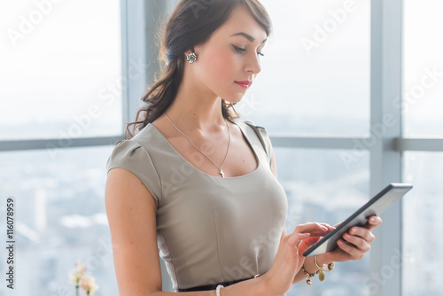 Fotografie, Obraz  Close-up portrait of a young attractive freelancer using tablet for telework, typing and reading new messages on-line
