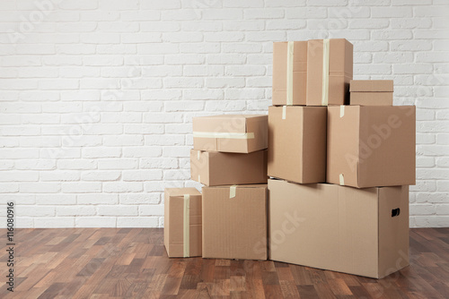 Fotografiet  Moving in. Stack of boxes in the empty room with copy space