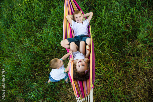 three children having fun in hammock
