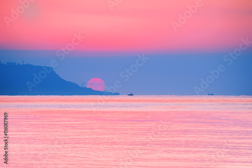 Candy pink sunrise over the sea. Bright colors huge sun coming out from behind the cape. Dalenko small boat on the horizon. Reflected red light on the water.