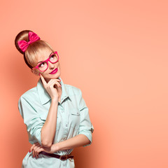 Naklejka Fashion. Nerd woman in Stylish Glasses Having Fun. Hipster fashion girl think, idea. Playful Blonde nerd with Glamour Pinup stylish Hairstyle, Trendy fashion Outfit, Red bow Makeup. Unusual Creative