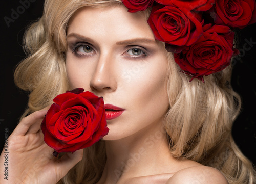 Leinwand Poster  Beautiful blond girl in dress and hat with roses, classic makeup, curls, red lips
