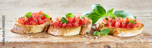 Foto  Delicious tomato bruschetta slices on a board
