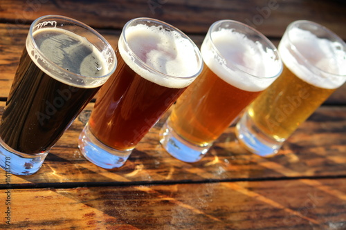 Four glasses of different craft beers on a wooden table during a tasting Poster