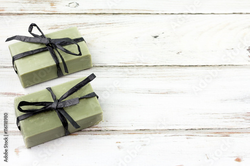 Fotografie, Obraz  Green Olive Oil Bar Soap Wrapped in Ribbon on White Distressed Wooden Background With Copy Space