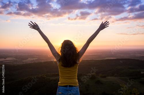 une jeune femme de dos , levant les bras face à un paysage sous le coucher de so Fototapeta
