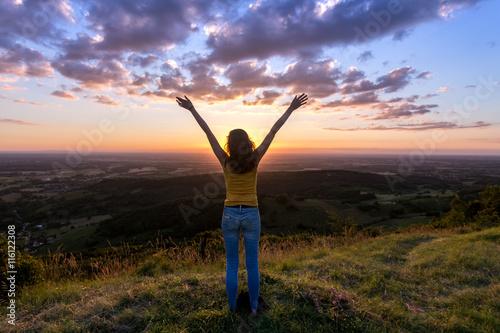 Fotografia une jeune femme de dos , levant les bras face à un coucher de soleil, en haut d'