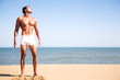 Young shirtless man standing on the beach