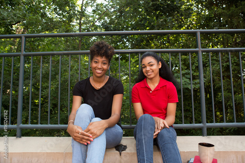 Fotografie, Obraz  2 young african american college students sitting on a sidewalk on campus