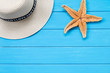 Straw hat and starfish on wood
