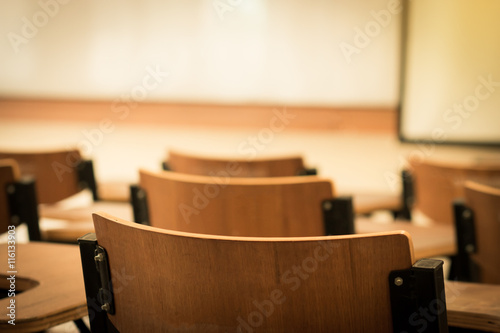 Chair in empty classroom, lecture armchairs in school, or colleg