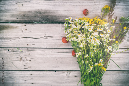 Staande foto Lelietje van dalen summer bouquet of daisies and Hypericum, with berries strawberries on wooden rustic background with copy space, wild flowers, medicinal herbs on an old table, top view