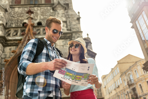 Positive tourists holding city map
