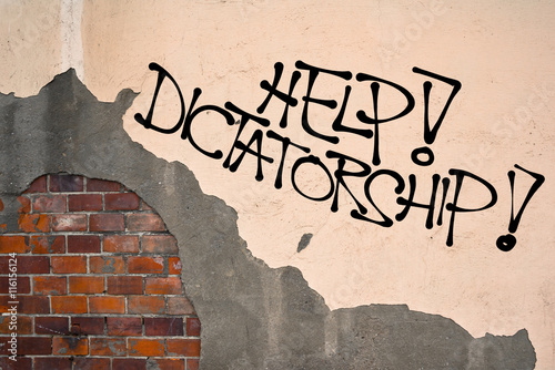 Fotografie, Obraz  Help! Dictatorship - Handwritten graffiti sprayed on the wall, anarchist aesthet