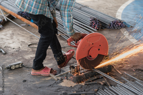 Fotografie, Obraz  Construction builder worker with grinder machine cutting metal reinforcement reb