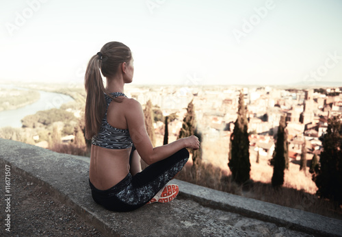 Fényképezés  Meditating girl in sportswear sitting on asphalt peak in the country