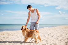 Handsome Man Standing With Dog On The Beach