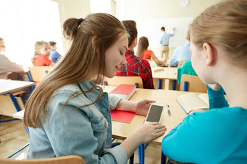 student girls with smartphone at school