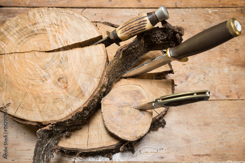 Spoed Foto op Canvas Jacht Hunting knives thrust in stumps on a wooden background