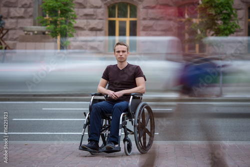 Vászonkép  The invalid man sit in the wheel chair in the crowd stream at the pavement