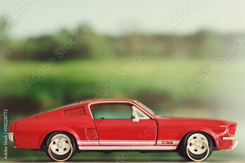 фотография  Wedding rings lie behind the wheels of a toy red Mustang