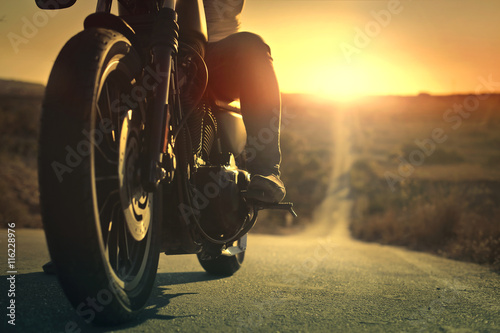 Fotografering  On a roaring motorcycle at sunset