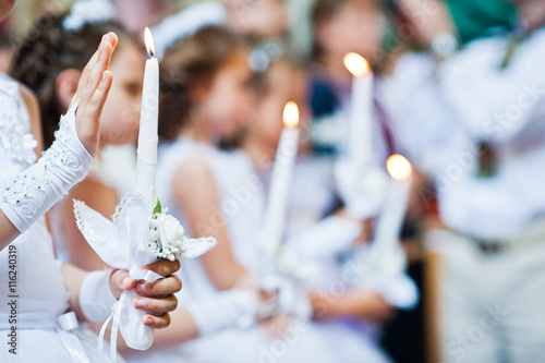 Fotografie, Obraz  Hands with candles of little girls on first holy communion