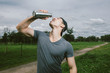 Young exhausted athlete drinking fresh water to refresh during