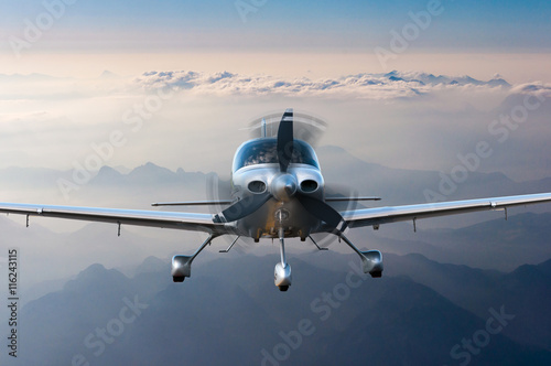 fototapeta na lodówkę Privat light airplane or aircraft fly on mountain background. VIP travel concept