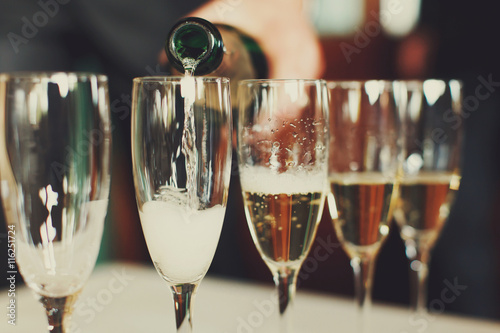 Man pours champagne in wineglasses Canvas-taulu
