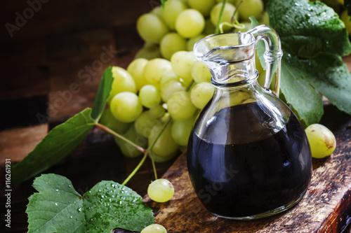 Balsamic vinegar in a glass jug, vintage wooden background, rust
