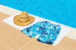 Hat and swimming trunks on towel near swimming pool